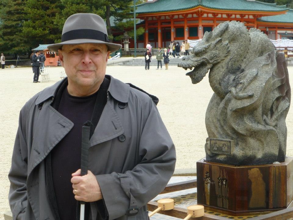 Stephen Kuusisto wearing a fedora and trench coat, standing beside a dragon in Kyoto, Japan